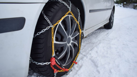 Car in winter season on the snow with chains on tires to provide traction