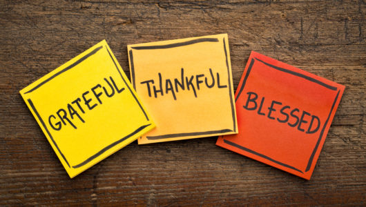 Grateful, thankful, blessed spiritual words - handwriting in black ink on sticky notes against rustic wood