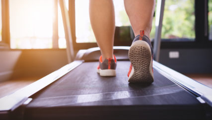 woman workout at gym,walking on treadmill equipment,exercise