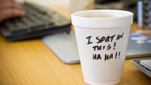 image of someone being intimidated at work, coffee cup inscribed with
