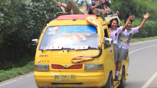 students are going to celebrate of finishing of school and moving to tourist place in the van - someone even on the roof of van