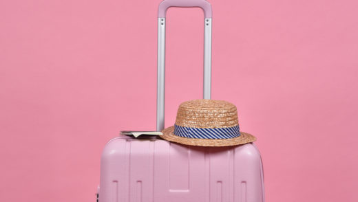 Pink suitcase and passport document over pink background