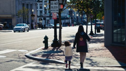 Working mother walking across street carrying one child and holding the hand of another
