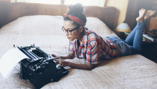 Young woman with eyeglasses, lumberjack shirt, jeans and headband lying on bed and using vintage typewriter.