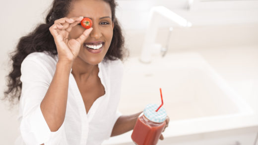Thirsty woman showing cherry tomato against her eye in right hand and holding fresh tomato juice in left.