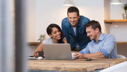 Coworkers smiling together while going through paperwork in office