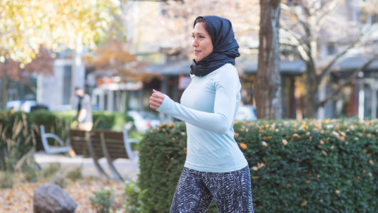 A woman wearing a headscarf and running clothes takes a jog through an urban environment. She is smiling.