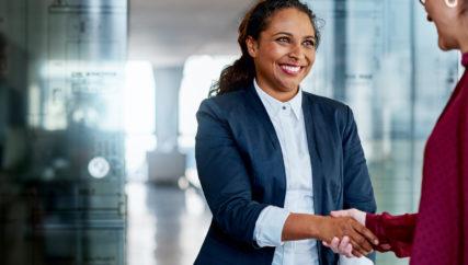 Shot of two businesswomen shaking hands in a modern office