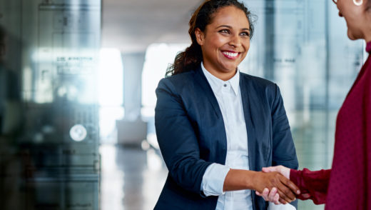 Shot of two businesswomen shaking hands in a modern office