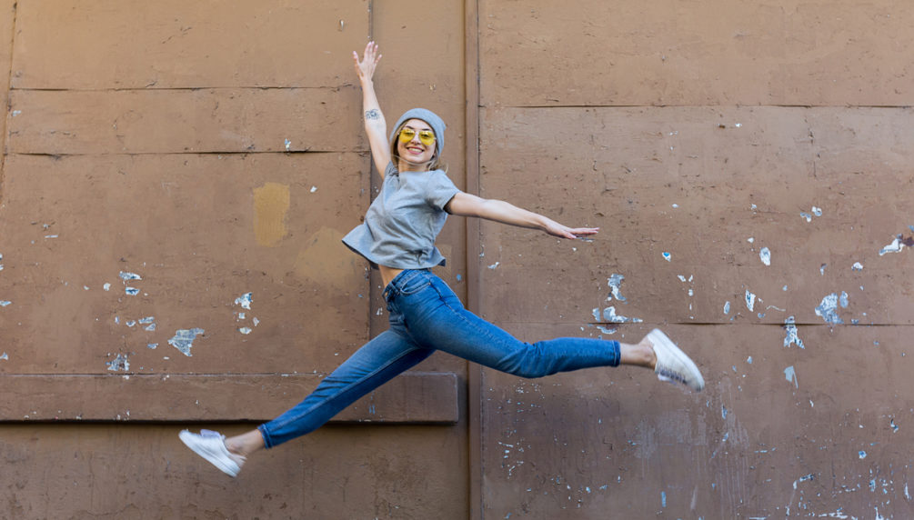 Young woman jumping front of wall