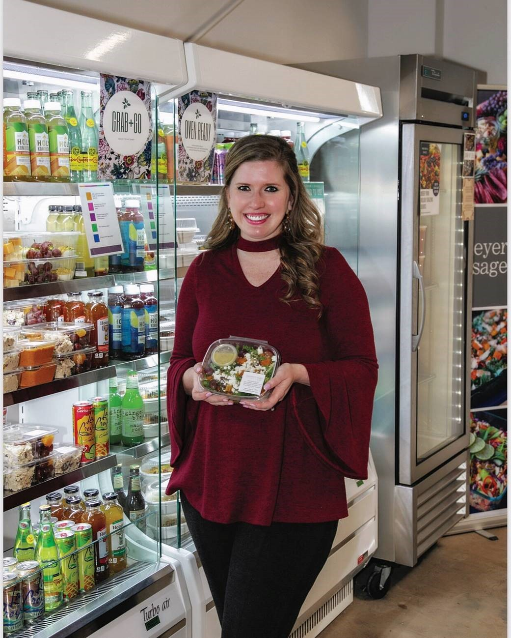 Callie standing in front of the grab'n'go section at Meyer and Sage