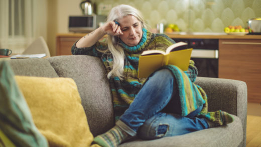 Mature woman is relaxing and reading a book