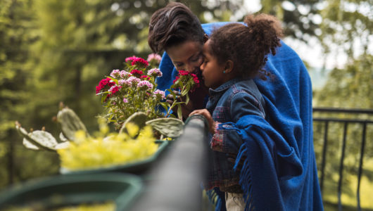 Young African American mother and daughter enjoying in a smell of flowers on a balcony.
