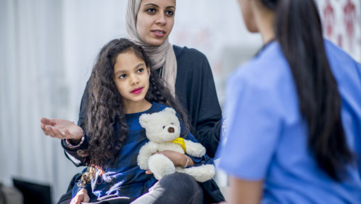 An Ethnic mother and daughter are indoors in a hospital. The girl is holding a teddy bear for comfort. The mother and doctor are talking about the girl's checkup.