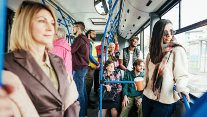 Multi ethnic group of people of all ages use public bus for commuting.