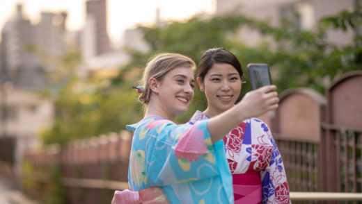 Multi-ethinic group of friends in yukata taking picture on slope