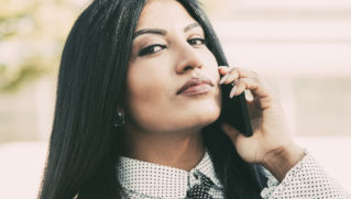 Arrogant confident businesswoman calling on phone and looking at camera. Serious young Hispanic female manager using mobile phone to connect client. Communication concept