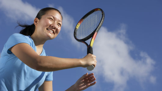 Happy young Asian woman tennis player holding racket after hitting forehand.