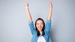 Amazed brunette young business woman in casual shirt is gesturing victory with her raised hands, she is shocked, extremely happy, with closed eyes, beaming smile, open mouth on grey background