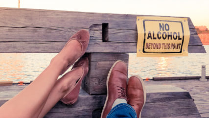 Concept of a young couple decided to stop consuming alcohol. Legs of a man and a women pointing to a sign ''No Alcohol beyond this point''