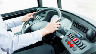 Bus driver in cockpit at the wheel driving