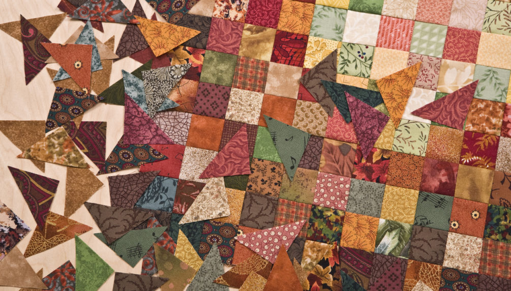 High resolution close up of tiny 1 inch square fabrics pieced together into a quilt.